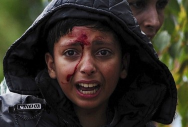 A girl cries after crossing Greece's border into Macedonia near Gevgelija, Macedonia, August 22, 2015. Thousands of migrants stormed across Macedonia's border on Saturday, overwhelming security forces who threw stun grenades and lashed out with batons in an increasingly futile bid to stem their flow through the Balkans to western Europe. Some had spent days in the open with little or no access to food or water after Macedonia on Thursday declared a state of emergency and sealed its borders to migrants, many of them refugees from war in Syria and other conflicts in the Middle East. REUTERS/Ognen Teofilovski - RTX1P7X4